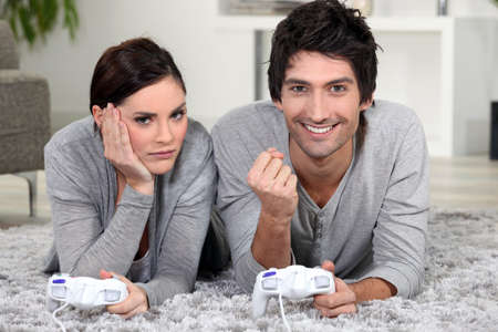 Couple laying down playing video games Stock Photo - 14106802
