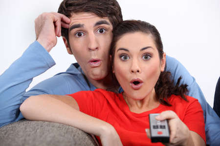 Shocked couple watching television photo
