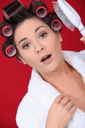 young woman with curlers on her hair photo