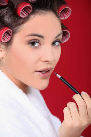 Woman wearing rollers and applying lip gloss photo