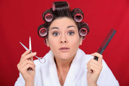 haircurlers: Woman with her hair in curlers holding scissors and a comb