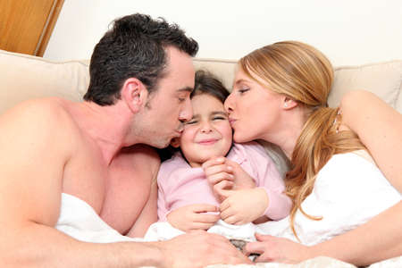 Young daughter in bed with parents Stock Photo - 14106652