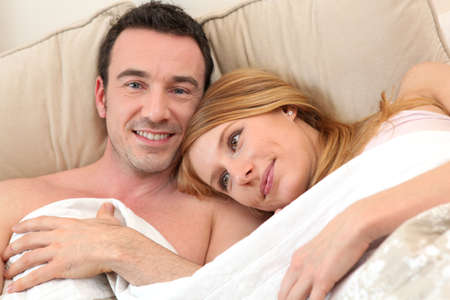 Smiling couple in bed photo