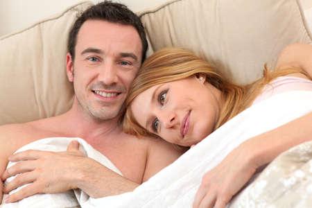 pareja apasionada: Sonriente pareja en la cama