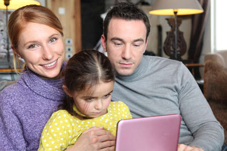 Parents and daughter sat with laptop on sofa photo