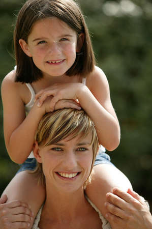 Young child riding on her mothers shoulders photo