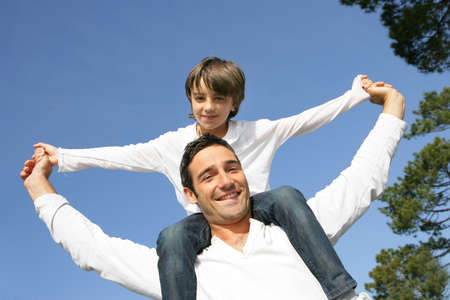 head on shoulder: Little boy riding on his fathers shoulders