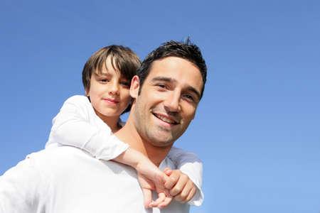 day of father: Boy guida piggy back sulla schiena del padre