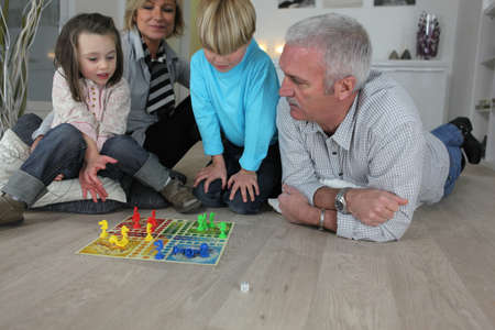 Couple playing a board game with their grandchildren photo