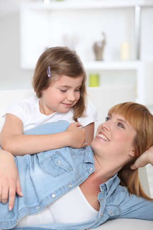 hairclip: Mother and daughter sat on couch Stock Photo