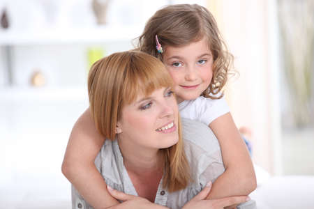 Child riding piggy back on her mothers back photo