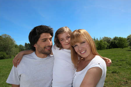 alike: Happy family enjoying a day out in the sunshine together Stock Photo