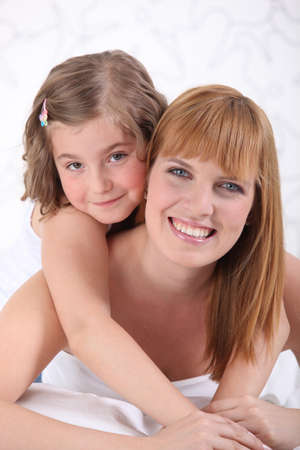 Mother and daughter laying on bed photo