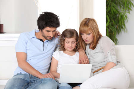 family sofa: Young family gathered on the sofa with laptop