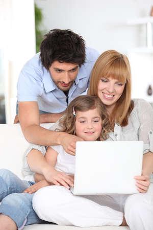madre trabajadora: Familia usando una computadora port�til Foto de archivo
