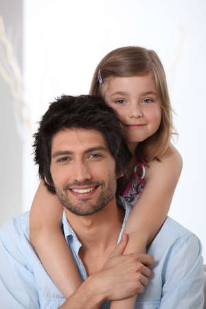 father daughter: Young girl riding piggy-back on her fathers back