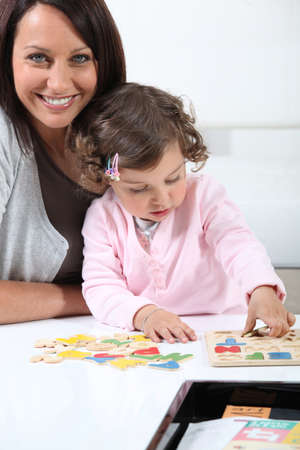 Mother with daughter doing puzzle Stock Photo - 14111027