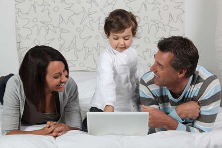 Parents and daughter in bed with laptop Stock Photo - 14111670