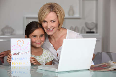 Mother and daughter in dining room with laptop photo