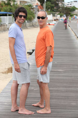 kinship: Grandfather and grandson walking along the beach