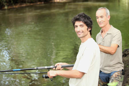 undisturbed: an old man and a young man angling beside a river