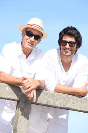 Two men in white leaning on a fence with a blue sky background