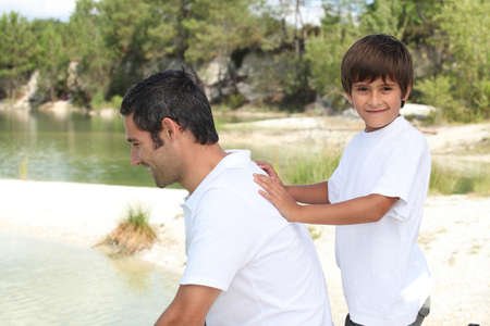 child pushing his father at the edge of a river photo