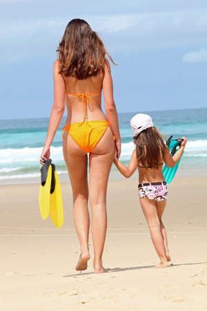 Mother and daughter going swimming in the sea photo