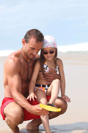 Father and daughter playing at the beach photo