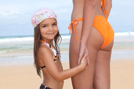 Girl on the beach holding hand of mother photo