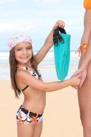 little girl holding mothers hand and showing flippers bag photo