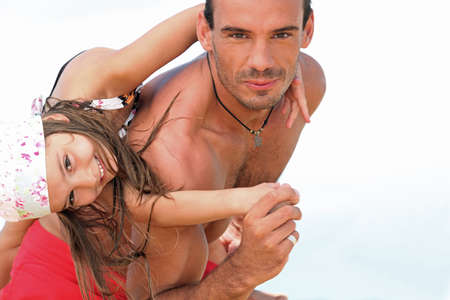 Father playing with daughter on beach photo