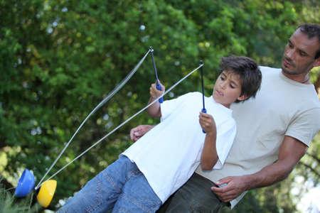 sacar la lengua: Hijo jugar con el diábolo Foto de archivo