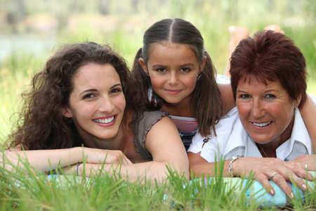 Grootmoeder, moeder en dochter liggen in het gras