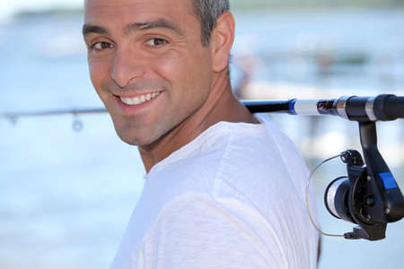 Man with fishing rod over his shoulder photo