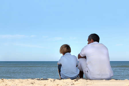 Father and son sitting on the edge of the ocean photo