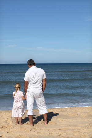 A father and his daughter looking at the sea. photo