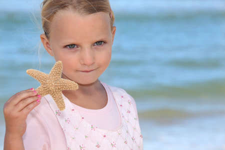 cute little girl holding starfish against sea background photo