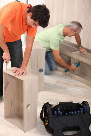 grandfather clock: Grandfather and grandson assembling furniture Stock Photo