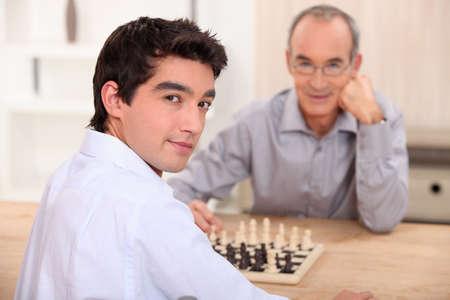 jugando ajedrez: Joven jugando al ajedrez con su abuelo