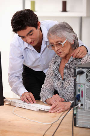 Grandson showing grandmother how to use computer photo
