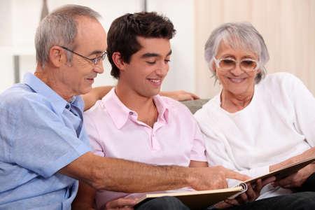 Grandparents and grandson watching photo album photo