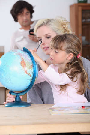 Mother and daughter looking at globe photo