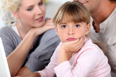 Bored little girl sat with her parents photo
