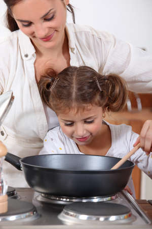 stew pan: Mother cooking with daughter