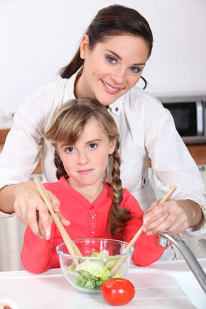 Mother and daughter preparing salad photo