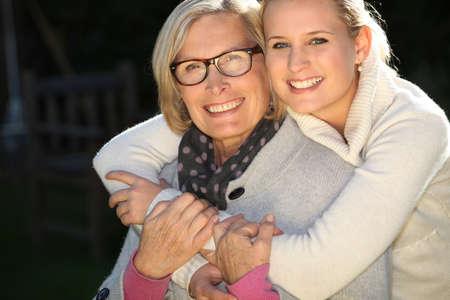 Girl embracing her grandmother photo
