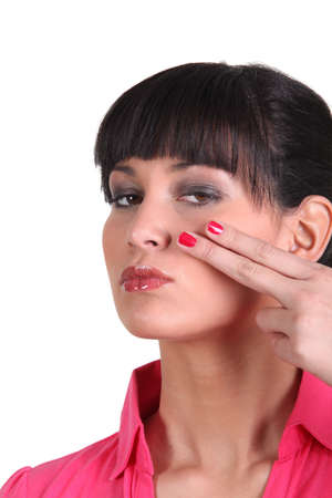 inconclusive: Brunette holding two finger to face
