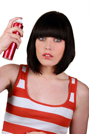 to lacquer: Woman spraying hair lacquer Stock Photo