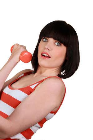 beauteous: brunette wearing striped sleeveless top lifting dumbbell